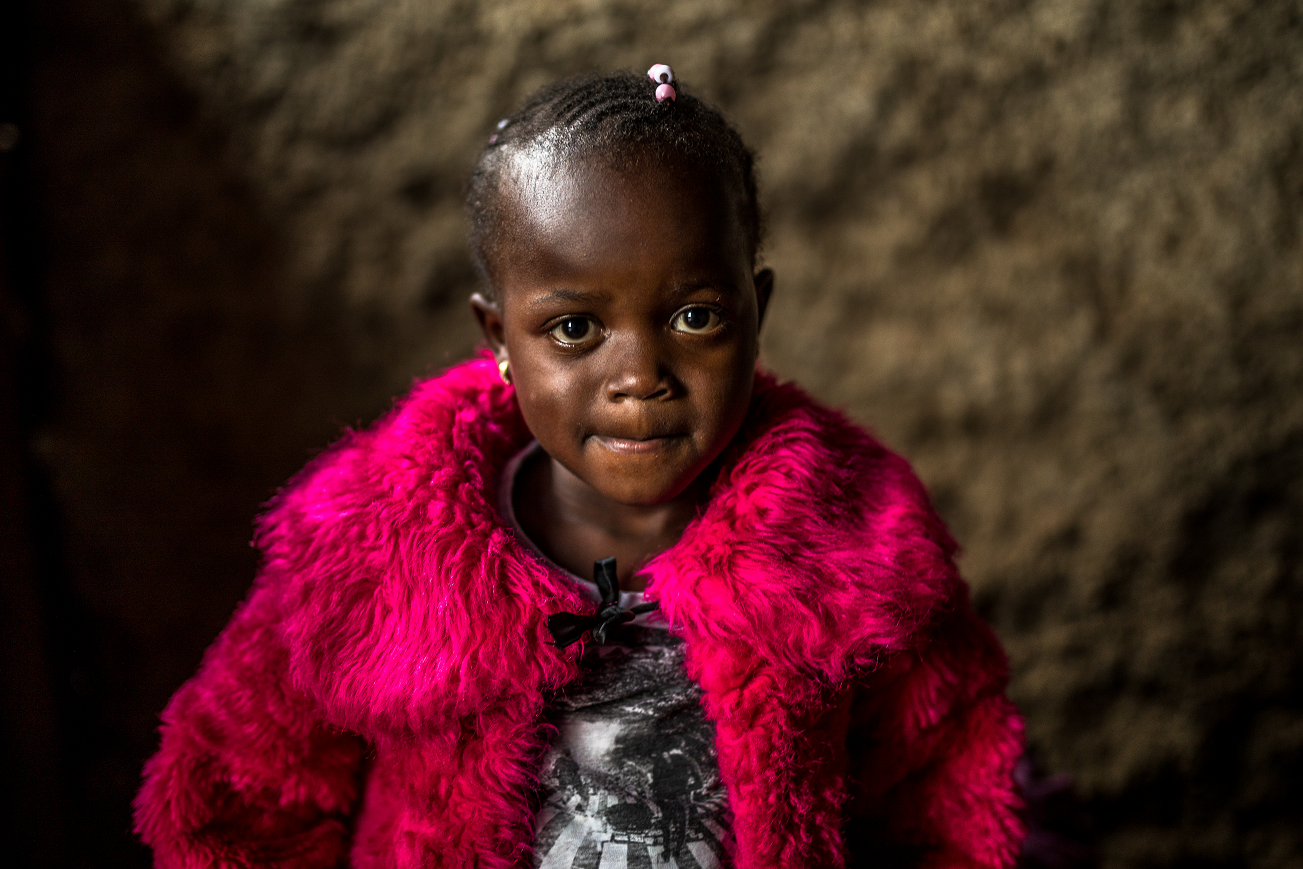 The photo shows Shazline, a four-year-old Kenyan girl with braided hair, looking into the camera, wearing a bright pink jacket.