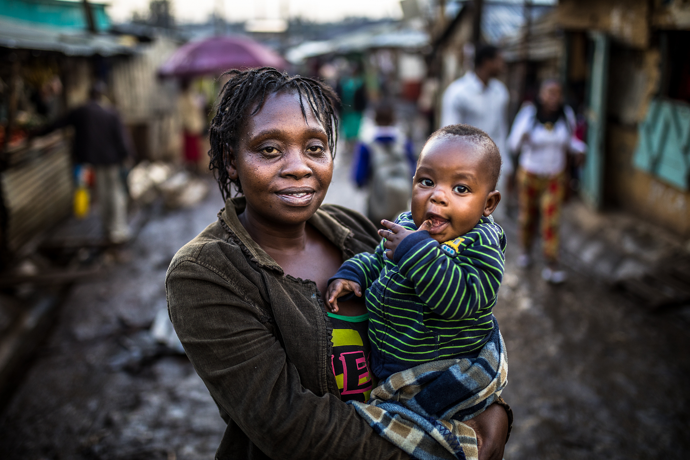 The photo shows Antoinette, a Kenyan woman with short dreads, smiling into the camera while holding her baby boy, also looking into the camera. In the background, there is an unpaved road in Kibera, muddy due to heavy rain falls.