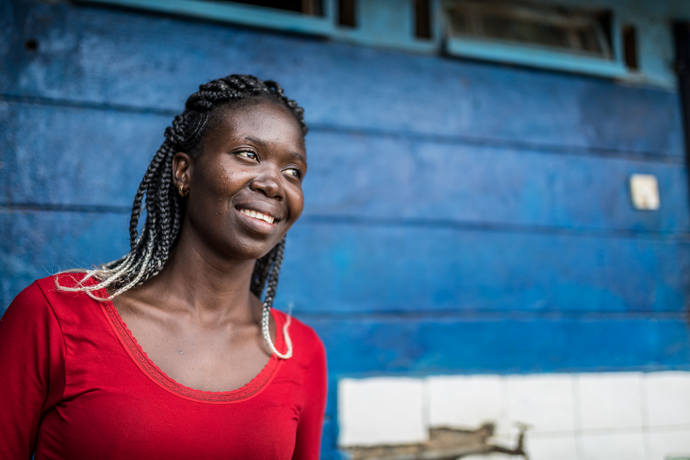 The photo shows Consolata, a 25-year-old Kenyan woman with long braided hair, against a blue wall, wearing a bright red shirt, smiling into distance.