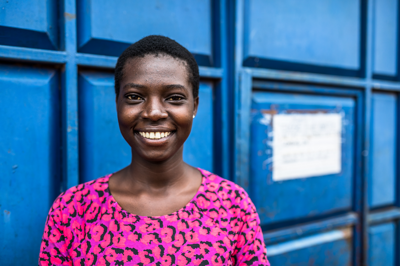 The photo shows Daphne, a 24-year-old Kenyan woman, short hair, in a pink shirt against a blue door, smiling into the camera.