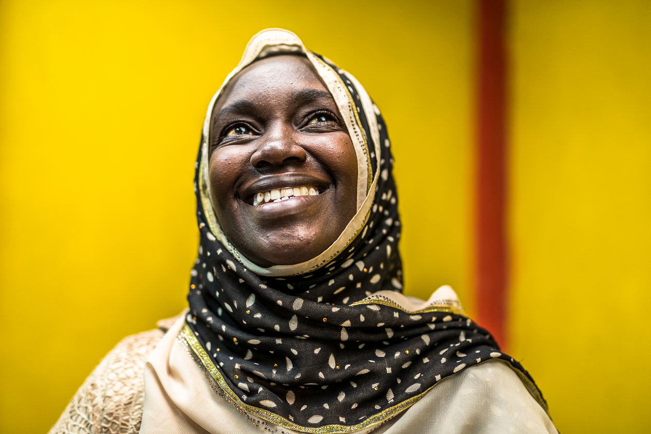 The photo shows the portrait of Rukia, a 35-year-old Kenyan woman, wearing a black/white headscarf and white clothes, smiling brightly and looking up to the sky.