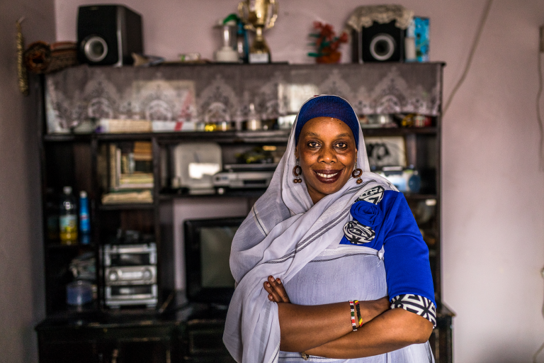The photo shows Siyama Ismail, a 43-year-old Kenyan woman in her living room. She wears blue and white clothing, headscarf, earrings, her arms crossed and smiling into the camera.