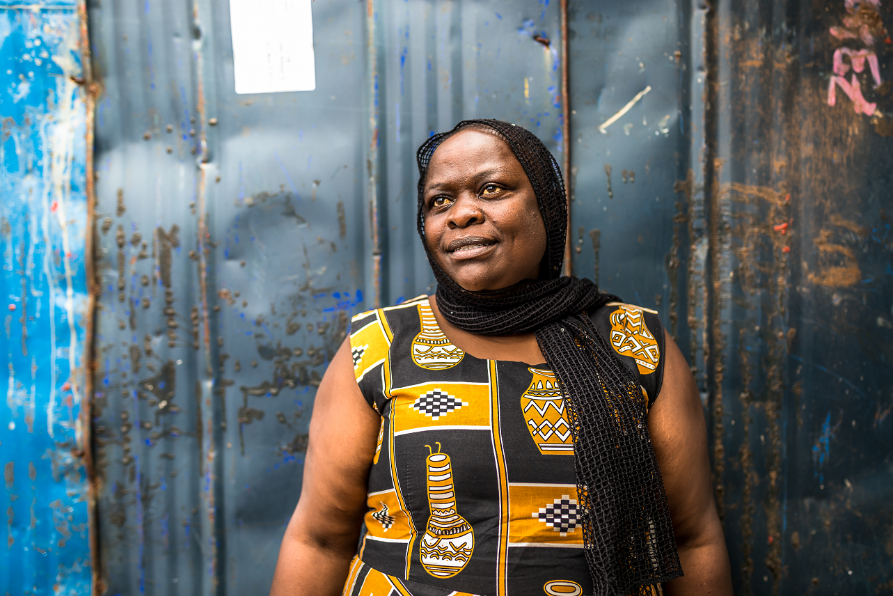 The photo shows Siama, a 43-year-old Kenyan woman, in a yellow-black dress against a dark blue wall, looking into the sky.