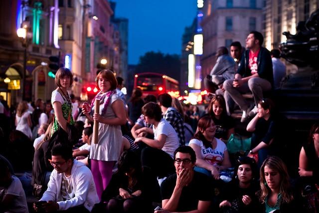 Bevölkerungsdynamiken: Gruppe junger Menschen am Piccadilly Circus in London bei Nacht