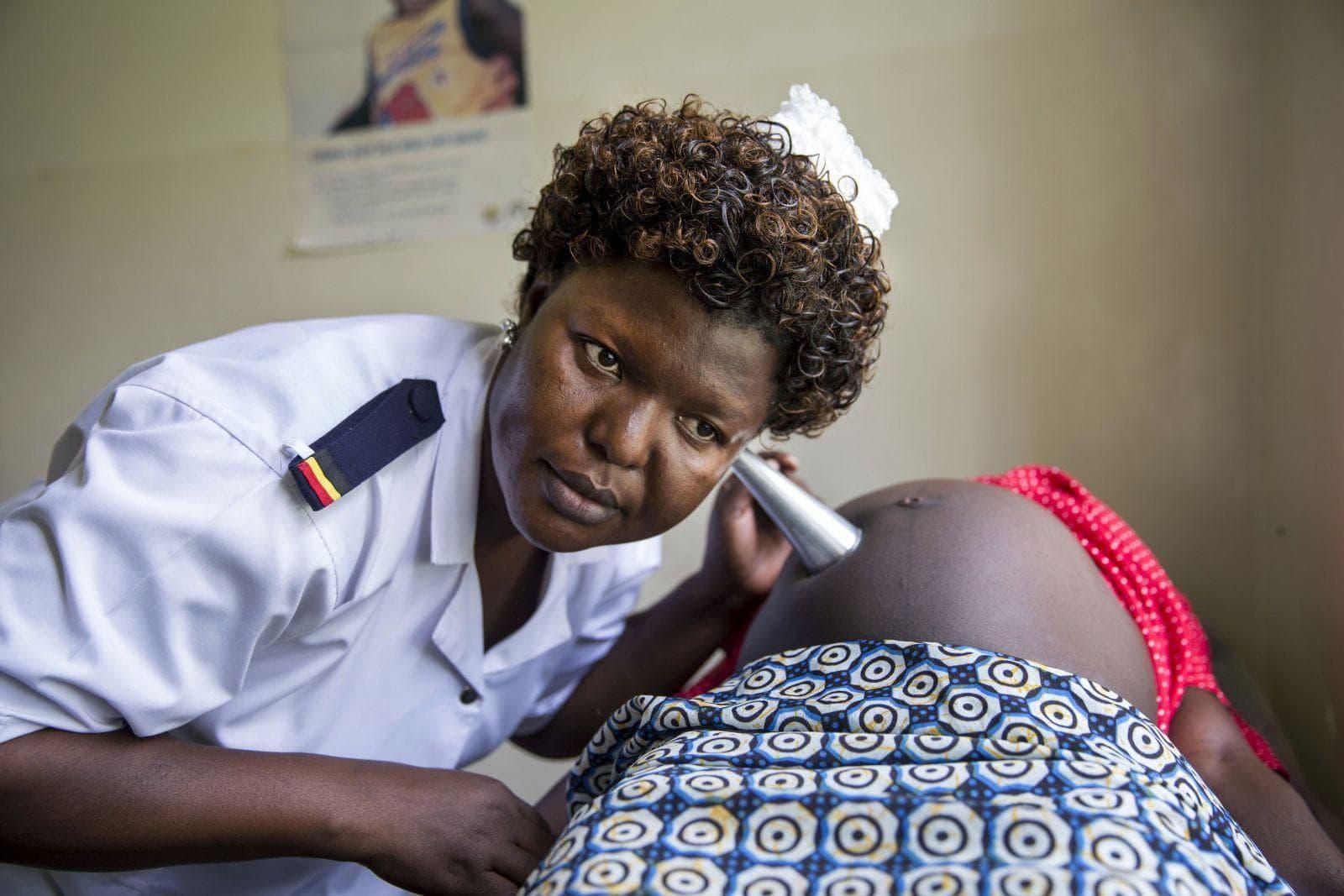 Eine Hebamme untersucht in Uganda eine Schwangere