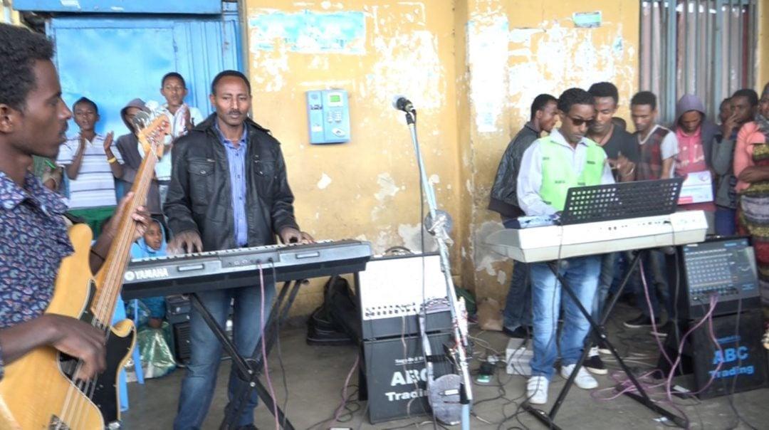 Eine Band mit Jugendlichen spielt mitten auf einem Busbahnhof in Äthiopien