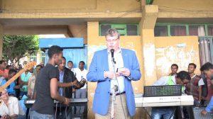 Knut Gerschau spricht zu den Jugendlichen an der Bushaltestelle