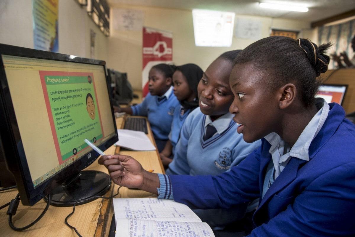Kenianische Schülerinnen sitzen vor einem Computerbildschirm