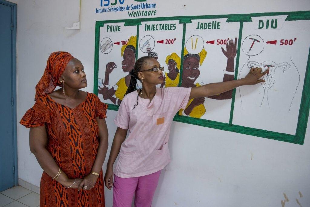 Eine Gesundheitsmitarbeiterin klärt im Senegal eine Frau anhand von Plakaten über die Gesundheit von Müttern und Verhütungsmöglichkeiten auf