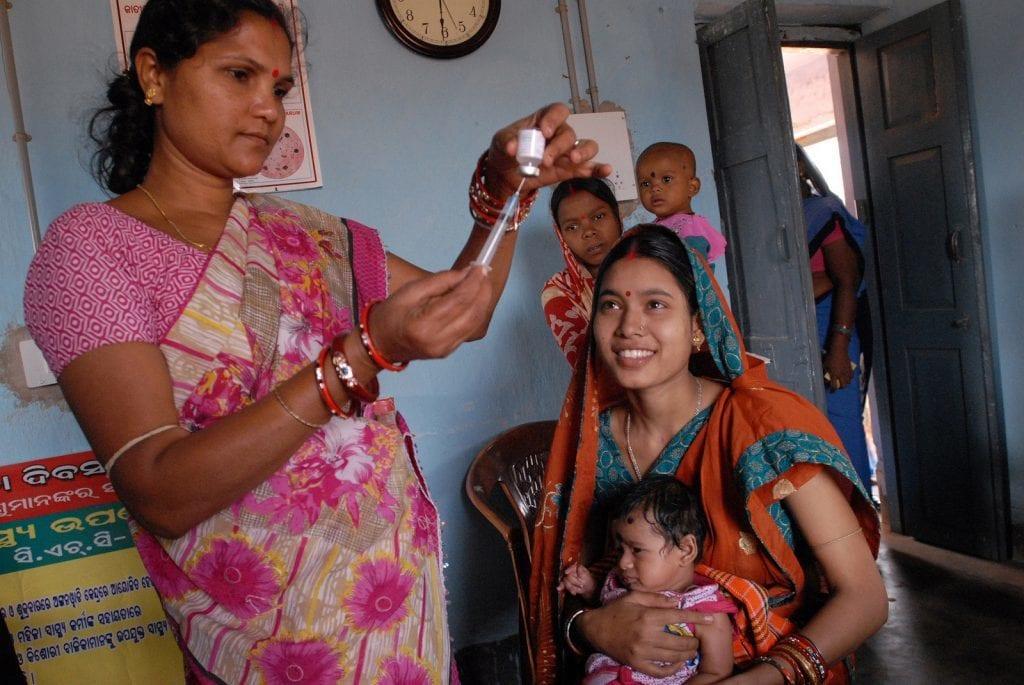 Eine Gesundheitsmitarbeiterin in Indien zieht eine Spritze auf. Daneben wartet eine Mutter mit einem kleinen Kind auf die Impfung.