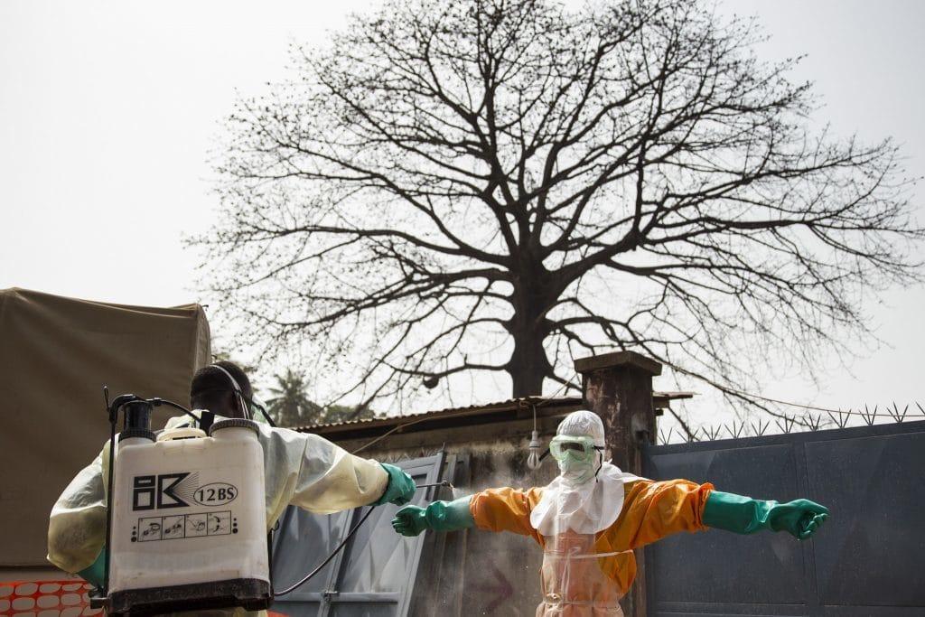 Ein Gesundheitsmitarbeiter in einem Schutzanzug wird während der Ebola-Epidemie 2015 in Guinea desinfiziert