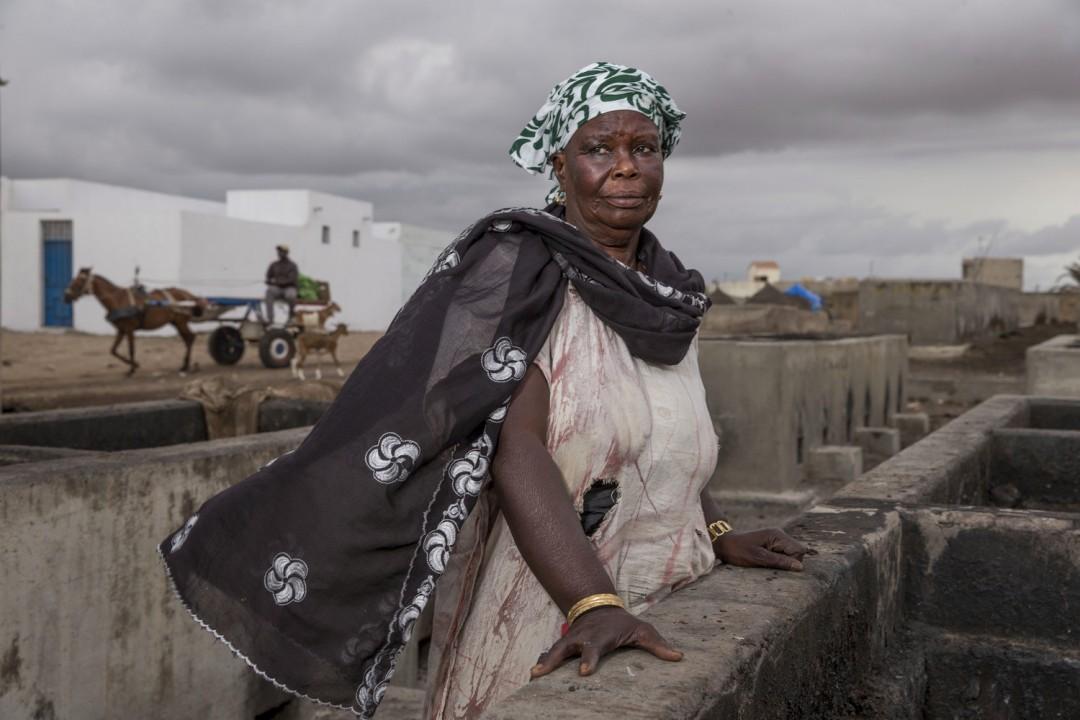 Ältere Frau steht an einer Brüstung im Senegal