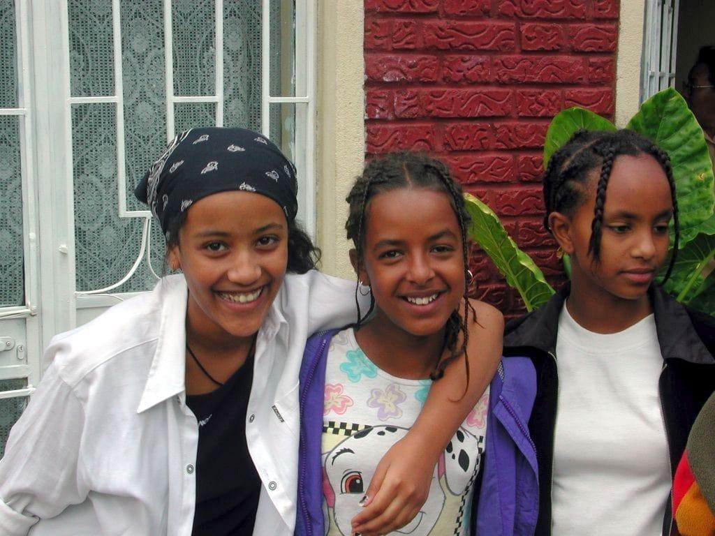 Drei äthiopische Mädchen vor einem Haus