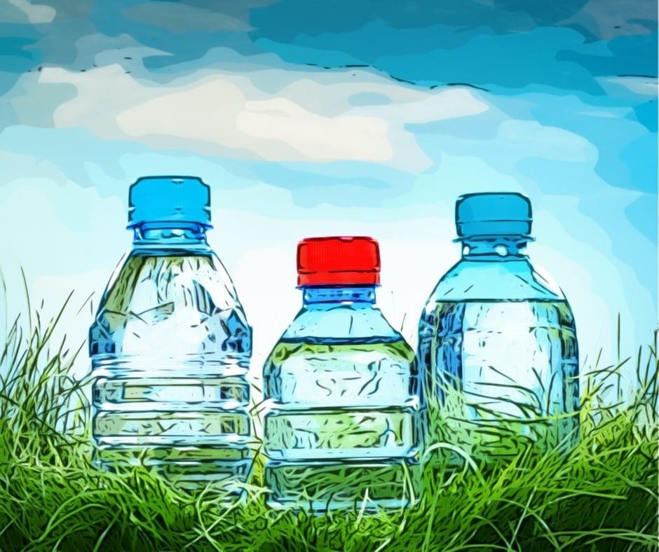 Drei Wasserflaschen im Gras vor blauem Himmel