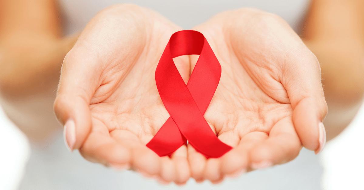 Zwei Hände, die eine Aids-Schleife halten
