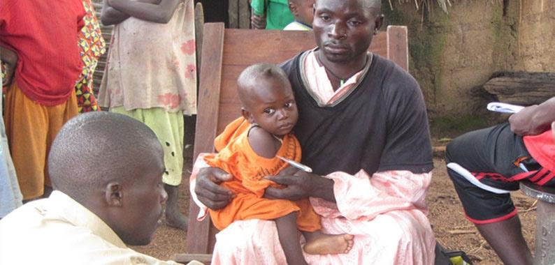Malaria: Kind in Afrika auf dem Arm des Vaters mit Fieberthermometer.