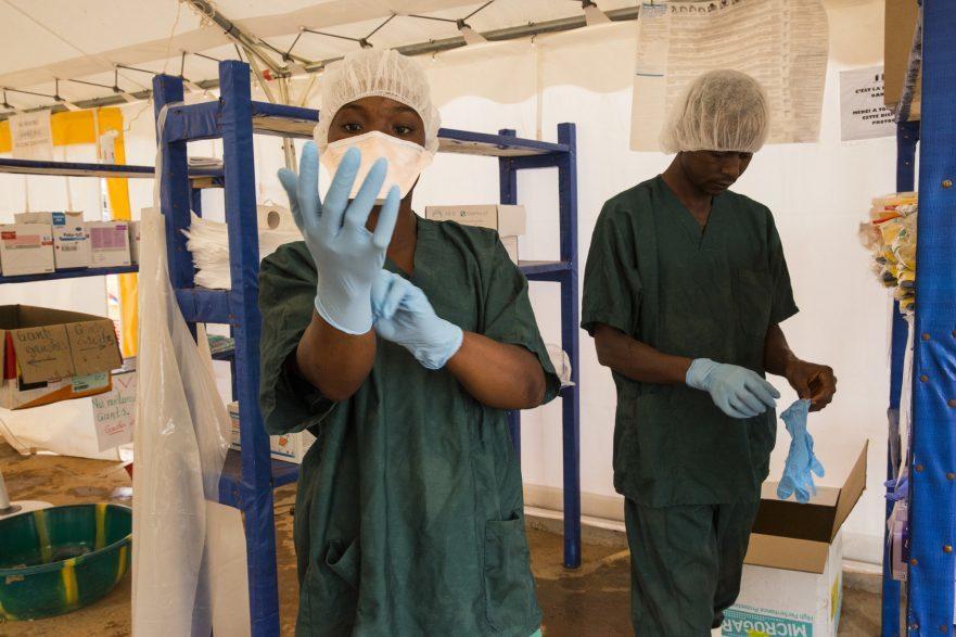 Zwei Helfer in Schutzkleidung im Behandlungszentrum für Ebola in Guinea