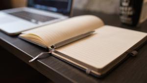 Arbeitstisch mit aufgeschlagenem Buch und Laptop.