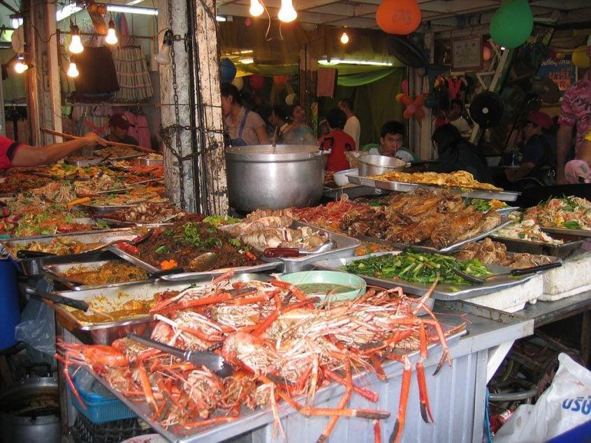 Verschiedene Lebensmittel auf den Tischen vor einer Garküche