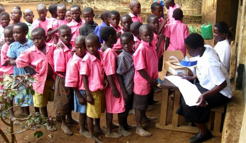 Eine Gruppe von Kindern in Uganda in pinken Kitteln warten vor dem Tisch einer Ärztin