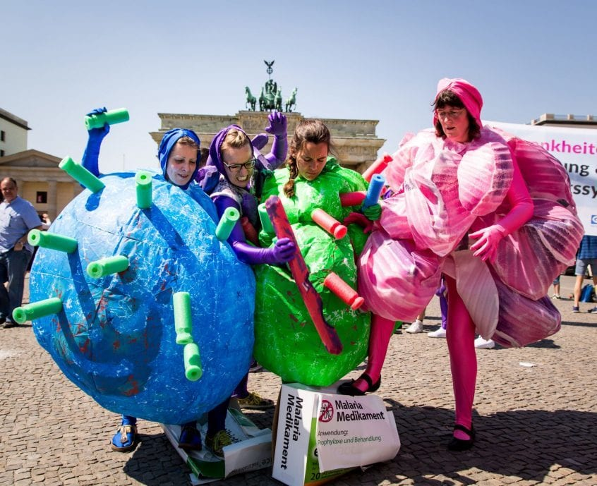 Als Viren und Bakterien verkleidete NGO-Mitarbeiter zertreten riesige Medikamentenpackungen vor dem Brandenburger Tor in Berlin