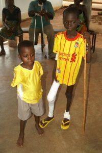Zwei Jungen in einem Krankenhaus in Togo. Einer hat ein bandagiertes Bein und läuft mit einem Stock.