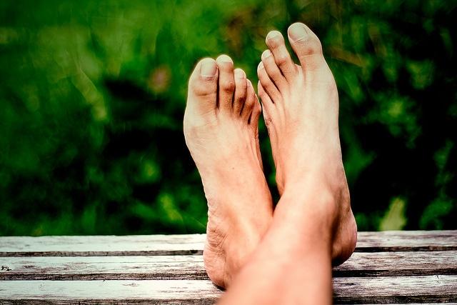 Nackte Füße auf einer Parkbank