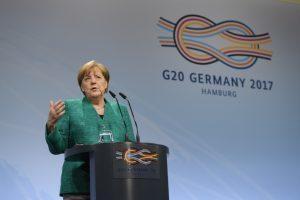 Bundeskanzlerin Angela Merkel mit dem G20-Logo bei der G20-Abschlusskonferenz in Hamburg