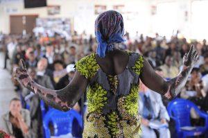 Eine von Gewalt gezeichnete Frau aus Ruanda erzählt vor Publikum ihre Geschichte