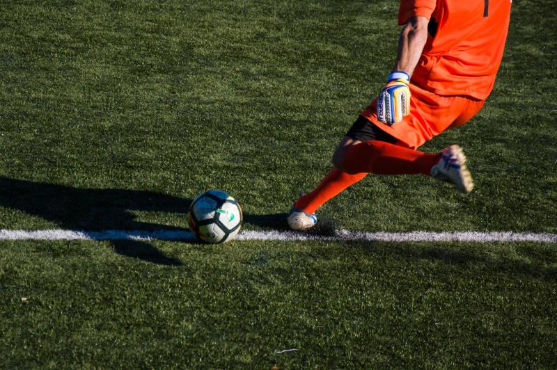 Fußballspieler in orangenem Trikot beim Abstoß auf der Torlinie