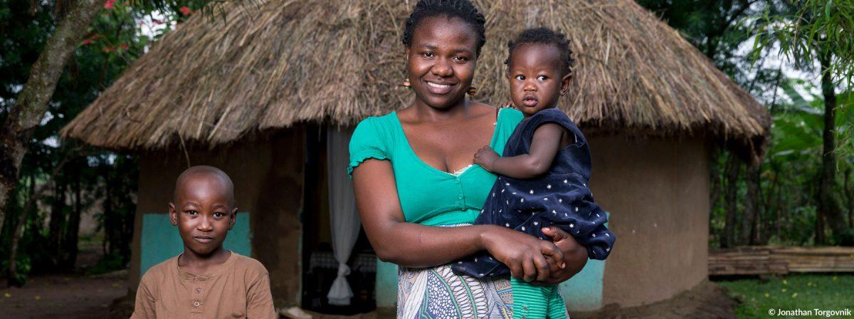 Eine Frau mit ihrer Tochte rund ihrem Sohn in Uganda.