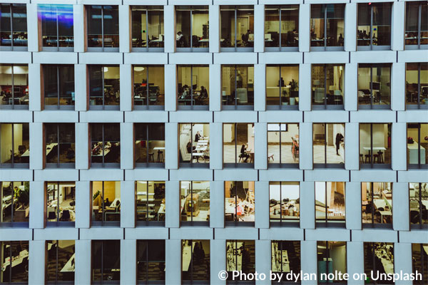 Ansicht einer Hochhausfassade mit zahlreichen beleuchteten Büros