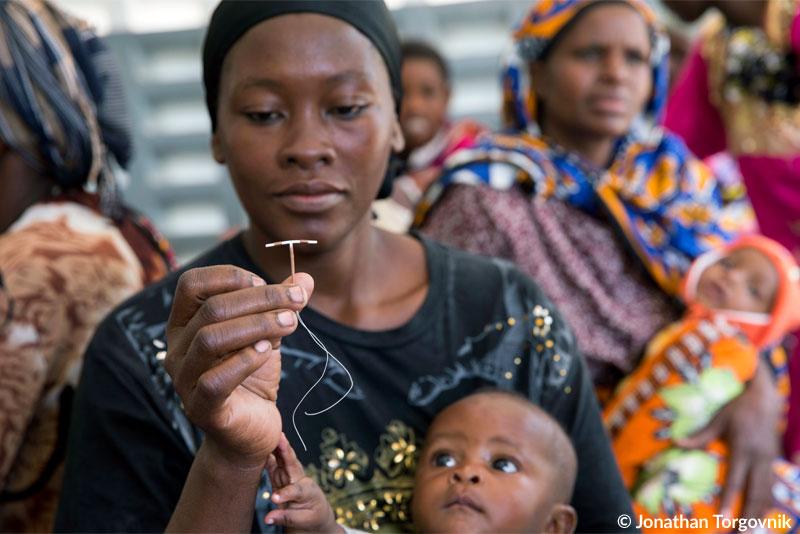 Eine kenianische Frau mit Baby auf dem Arm hält in einer Gesundheitseinrichtung in Rabai (Kenia) eine Kupferspirale in der Hand – damit können Frauen langfristig verhüten.