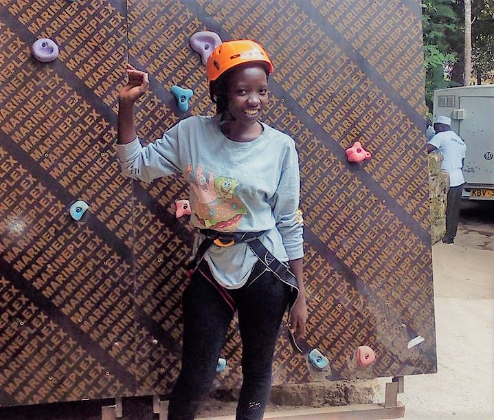 Jugendberaterin Silvia aus Kenia vor einer Kletterwand.