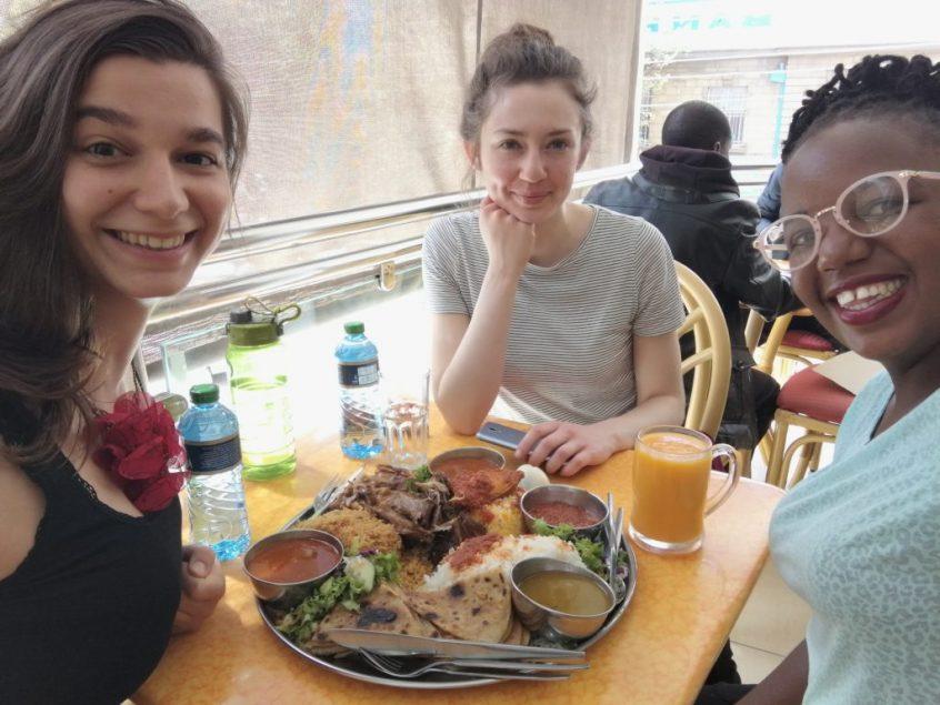 Drei Frauen sitzen beim Gespräch über Aufklärung und Verhütung in einem Restaurant am Tisch.