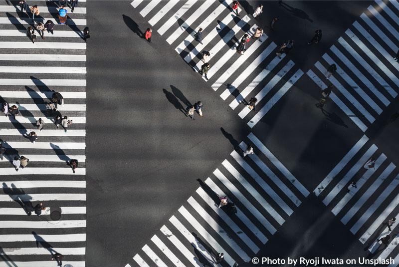 Vogelperspektive: Menschen laufen auf Zebrastreifen in einer Stadt über eine riesige Kreuzung.