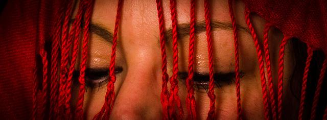 Ausschnitt der Augen einer Frau über deren Gesicht rote Fäden hängen.